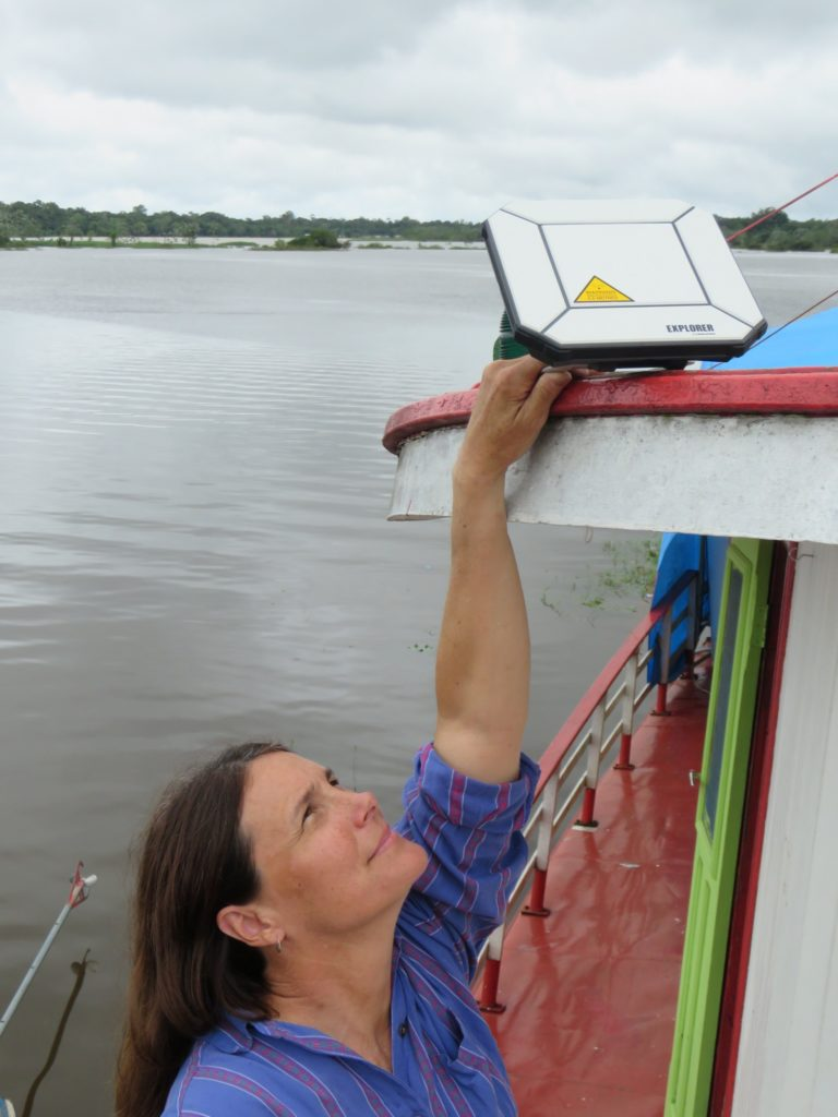 Laura adjusts the signal for the satellite hub so that Houseboat Amazon can send photos and email. (Photo courtesy of Laura K. Marsh)