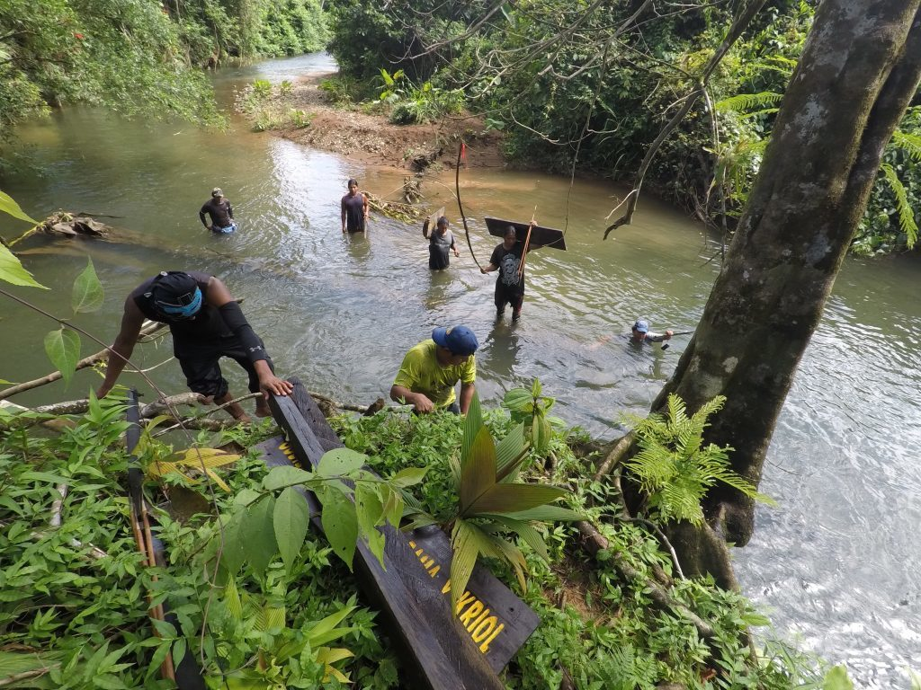 Rama community members carrying a sign into the forest for installation after the hurricane. (Photo by Yoharlyn Martinez)