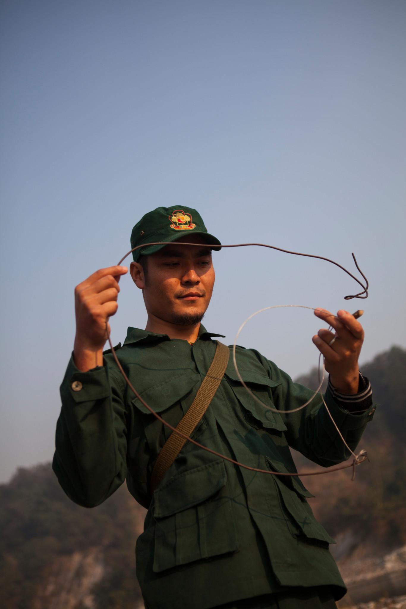 A ranger holding a poachers snare. Royal Manas National Park, Bhutan.