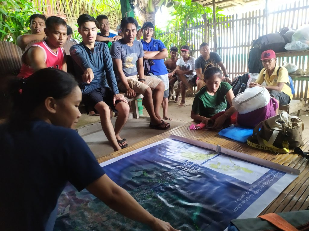 A community meeting with people gathered around a map.
