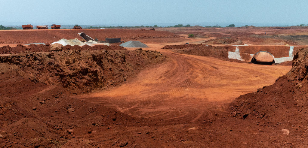 A bauxite mine that has completely destroyed the forest that once stood in the same spot. Now, only red soil remains.
