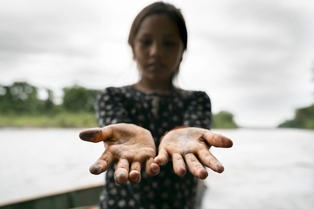 A girl holds out her hands dotted with oil from a spill contaminating the river behind her.